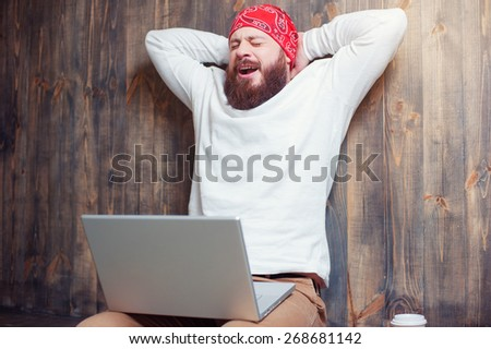 So tired! Young bearded man working on laptop and yawning while sitting against wooden wall. - stock photo