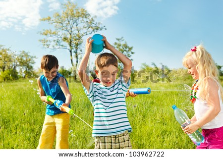 Soaked happy kids playing with water in the meadow - stock photo