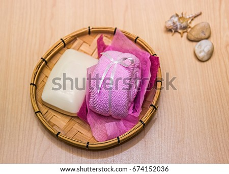Soap and a towel on a light wooden background. Sea stones and shells in the background.