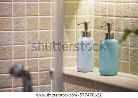 Soap And Shampoo Dispensers On A Shelf Inside A Shower Box / Bathroom