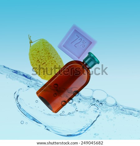 Soap, bottle of shampoo and sponge in water on blue background - stock photo