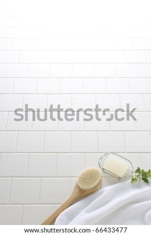 Soap,brush,and towel on white tile floor - stock photo