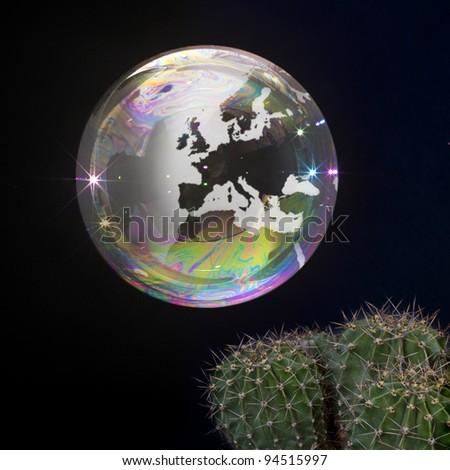 Soap bubble Earth floats close to a cactus. Fragile Earth. - stock photo