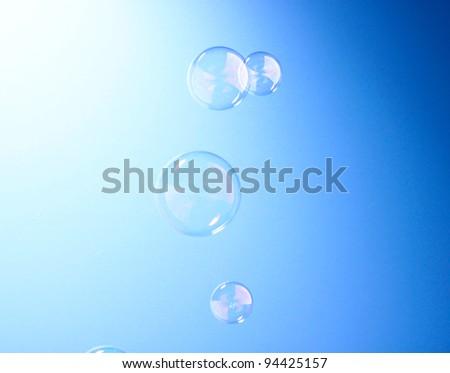Soap bubble on blue background - stock photo