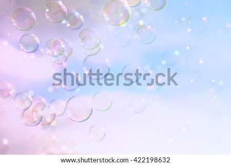 Soap bubbles floating in the air against soft clouds and sky. filtered image. selective focus - stock photo