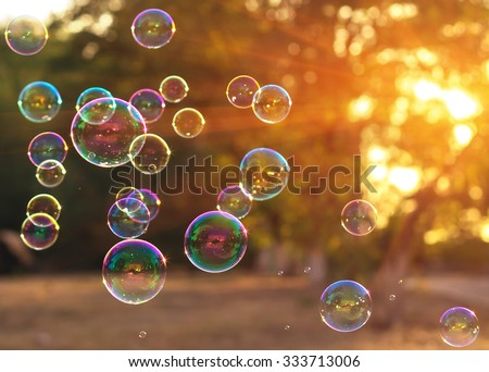 soap bubbles into the sunset with beautiful bokeh - stock photo