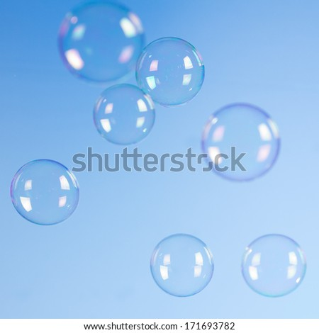 Soap bubbles isolated on blue background - stock photo