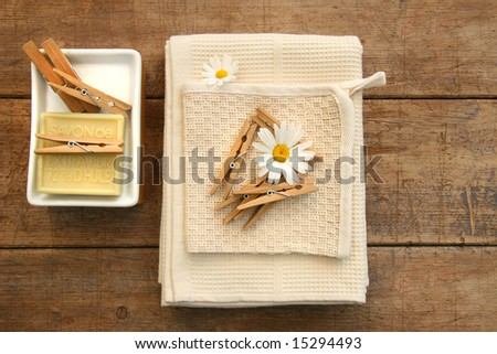 Soap, clothespins and towels on rustic table - stock photo