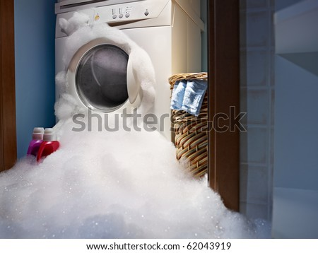 soap coming out from broken washing machine. - stock photo