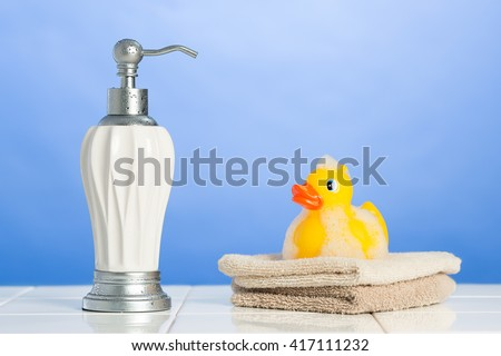 Soap dispenser with face cloths and rubber duck - stock photo