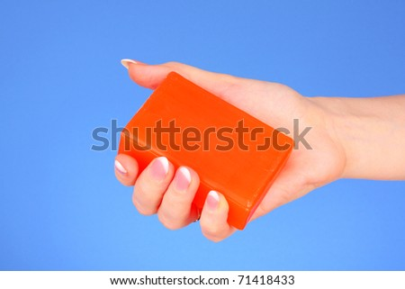 Soap in hand  on blue background - stock photo