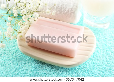 Soap on a dish over towel background, close up - stock photo
