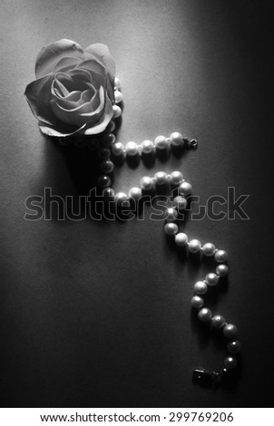 soap rose and pearl necklace on white background in black and white