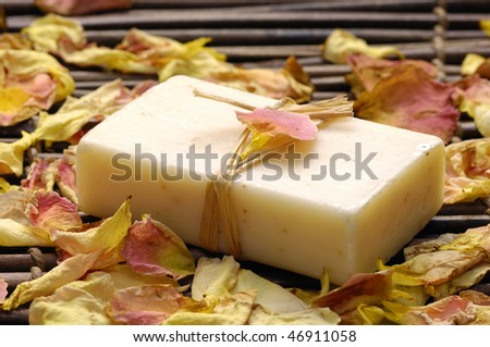 soap with rose petals on bamboo mat - stock photo