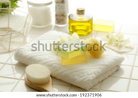 Soaps, oils and a brush laid out with a towel on a bathroom counter. - stock photo