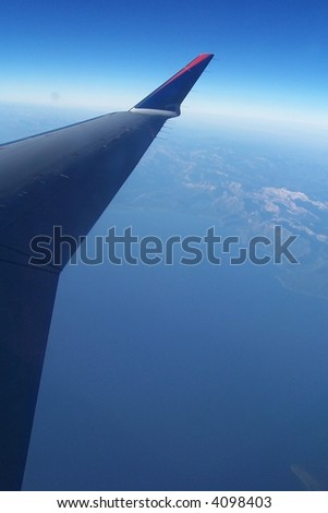 soaring airplane wing over lake