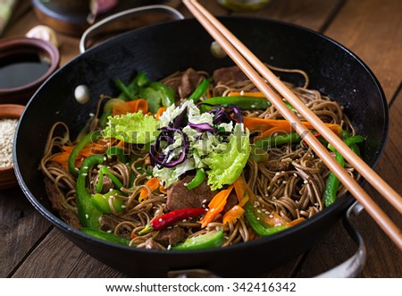Soba noodles with beef, carrots, onions and sweet peppers - stock photo