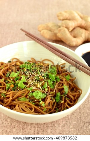 Soba noodles with soy sauce, ginger and garlic. Garnished with chopped parsley and sesame seeds - stock photo
