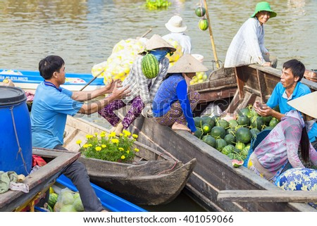 Soc Trang, Vietnam - February 3rd, 2016: Farmers throw your watermelon for goods at floating market is the market early on agricultural trade practices River area of Soc Trang, Vietnam - stock photo