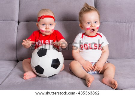 Soccer baby twins fans of Poland team in national colors - stock photo