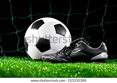 soccer ball and cleats on the football field