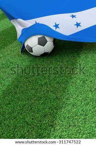Soccer ball and national flag of Honduras lies on the green grass - stock photo