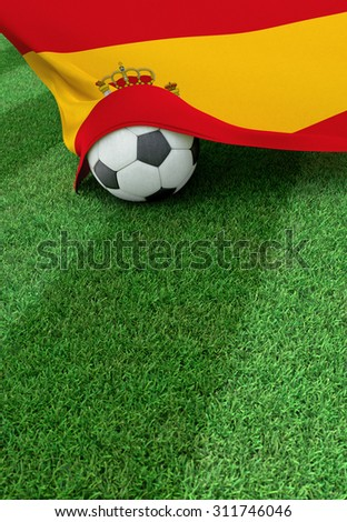 Soccer ball and national flag of Spain lies on the green grass