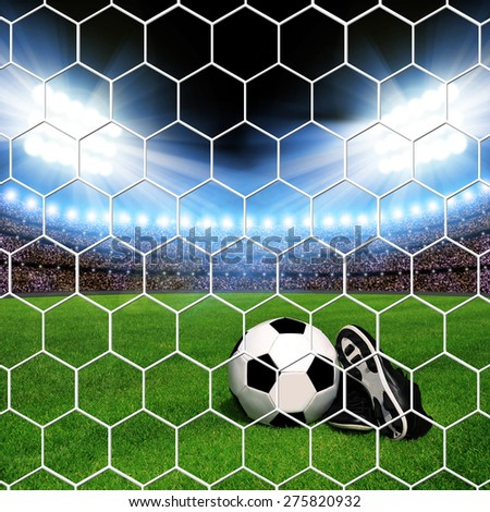 Soccer ball and shoes in grass, soccer stadium with the dright lights. - stock photo