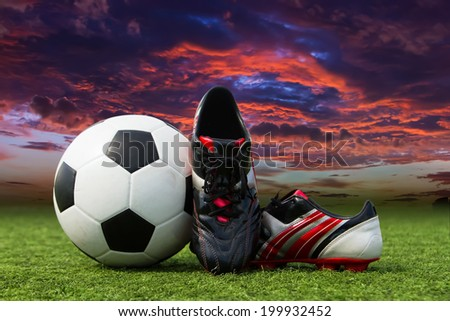 Soccer ball and soccer shoes on the field of green grass. - stock photo