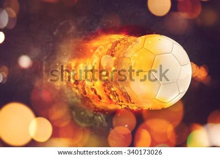 Soccer ball burning in flames, penalty kick football flying towards the goal. - stock photo
