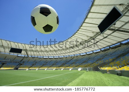 Soccer ball flying over bright green grass football pitch - stock photo