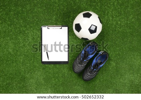 Soccer ball, football boots, notebook or chart notes and pen in the grass