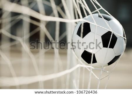Soccer ball going into goal net ,selective focus - stock photo