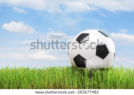 Soccer ball in a green grass field with sky and clouds in the background - stock photo