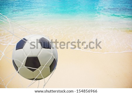 Soccer ball in a net on beach background - stock photo