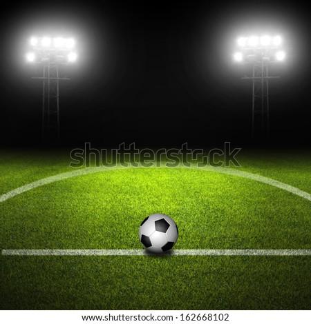 Soccer ball in field with illuminated stadium lights - stock photo