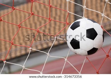 soccer ball in goal on stadium background - stock photo