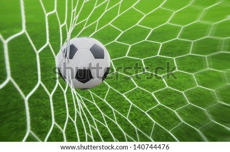 soccer ball in goal with green background - stock photo