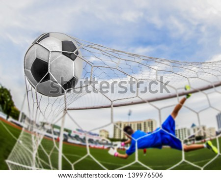soccer ball in goal with loss goalmam - stock photo