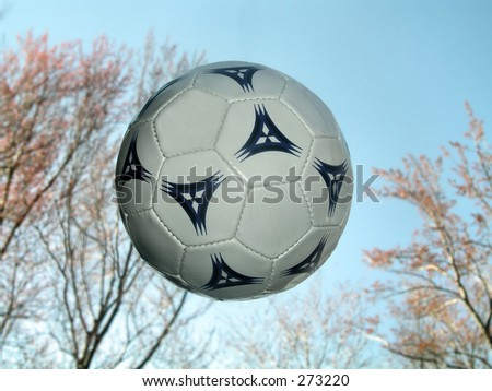 Soccer ball in the air with sky and trees in background - stock photo
