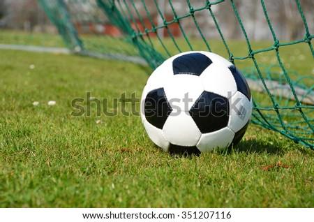 Soccer ball in the goal net - stock photo