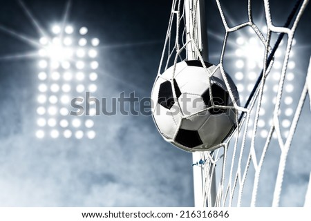 Soccer ball in the goal net with stadium lights in the background - stock photo