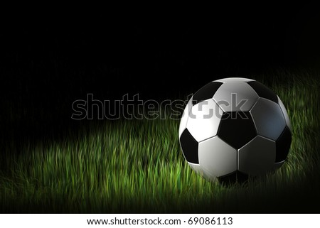 Soccer ball in the green grass at night - stock photo