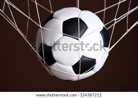 Soccer ball in the net on brown background - stock photo
