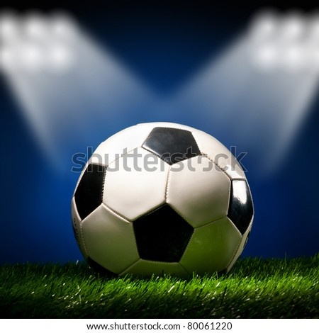 soccer ball is lying on grass on field at stadium - stock photo