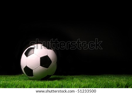 Soccer ball on grass against black background - stock photo
