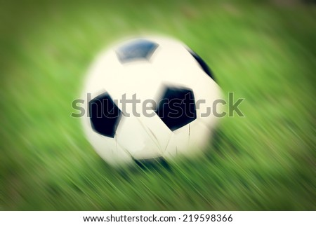 soccer ball on grass in the evening. - stock photo