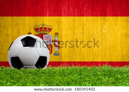 Soccer ball on grass with Spain flag background close up