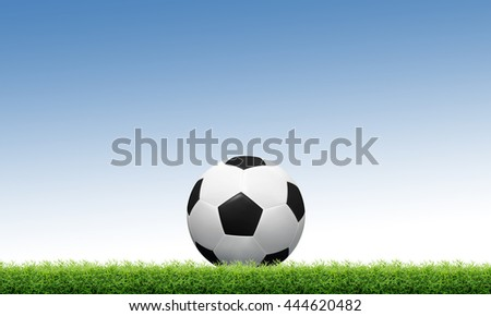 Soccer ball on green grass and blue sky background with clipping path.