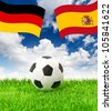 soccer ball on green grass and national flags of germany and spain over dramatic blue sky - stock photo